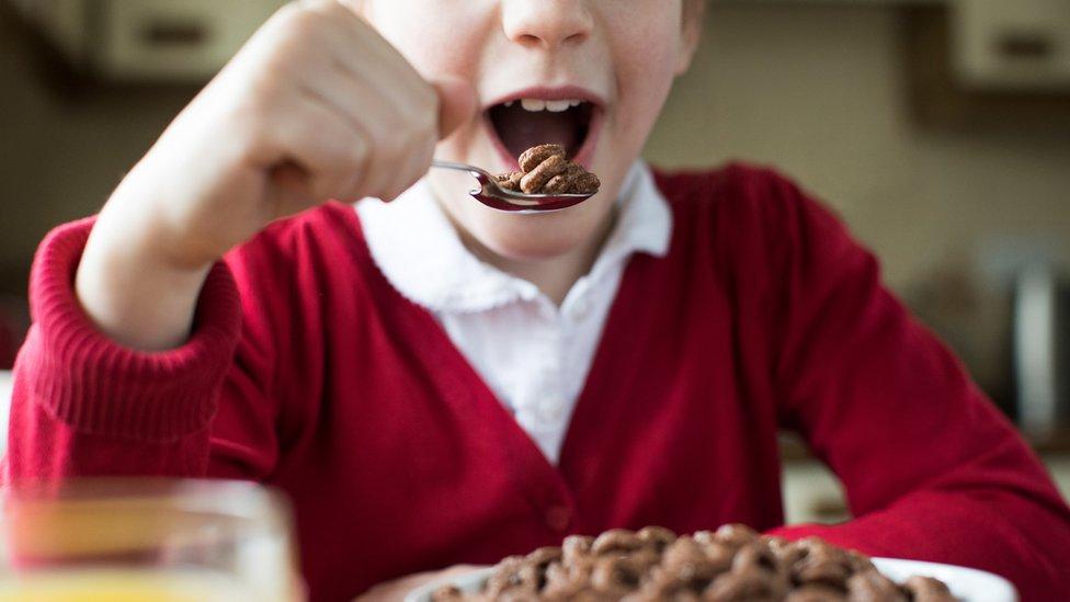 Niño comiendo cereales.