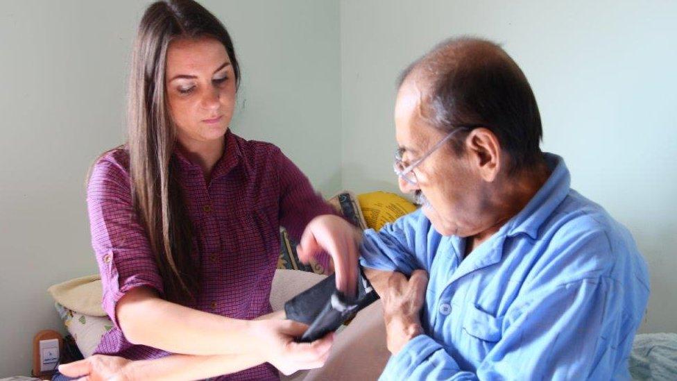 Doktorka meri pritisak pacijentu