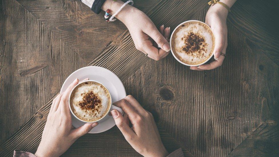 Dos personas tomando café.