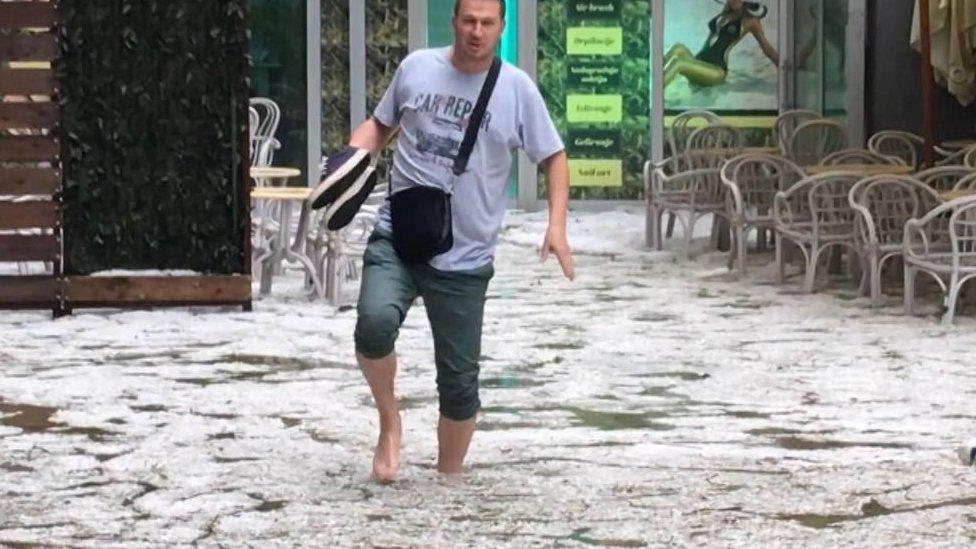 Stanovnik Užica hoda potopljenom ulicom