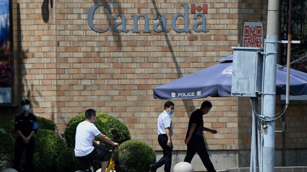 Gente pasando frente a la Embajada de Canadá en Pekín el 10 de agosto de 2021.