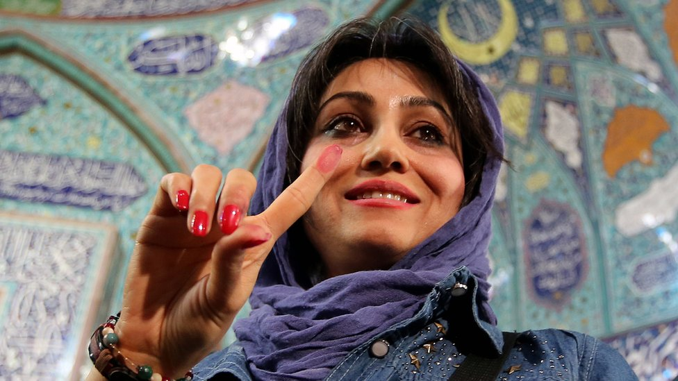 An Iranian woman displays her ink-stained finger after casting her ballot for both parliamentary elections and the Assembly of Experts at a polling station in Tehran, Iran