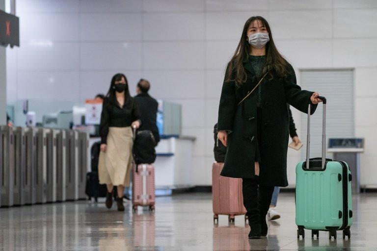 Mujeres asiáticas con barbijo en una terminal de transporte.