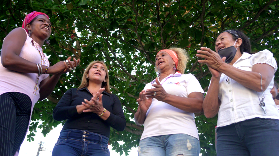 Mujeres del Planton, gathered in a circle, singing the bullerengue under a tree