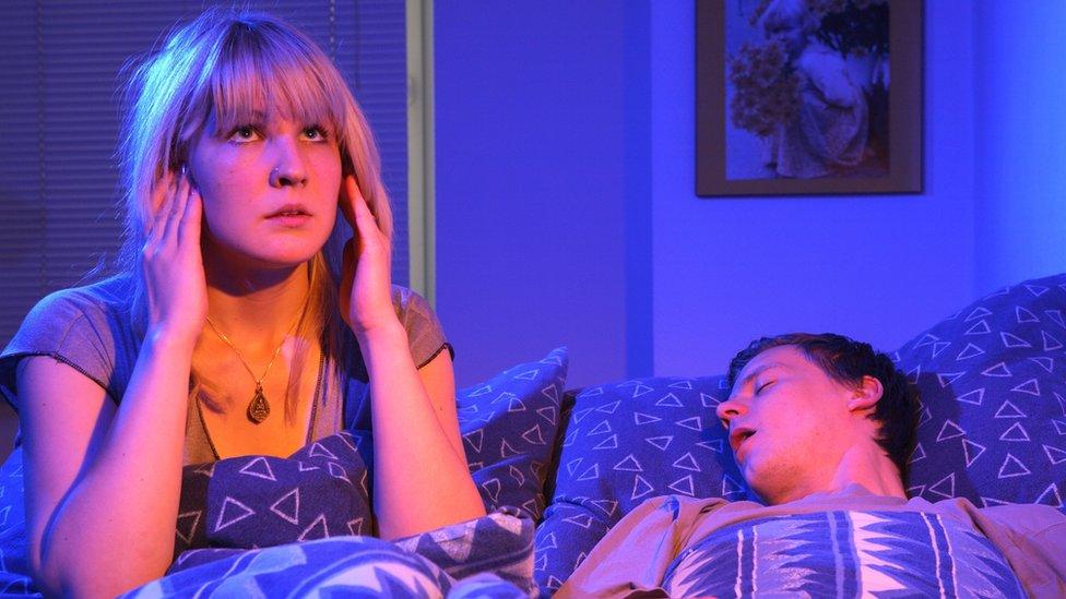 Žena u krevetu pored muškarca koji hrče