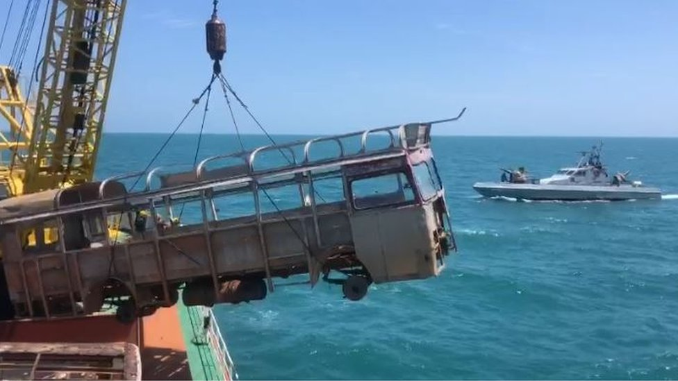 A boat dumping a old bus into the sea