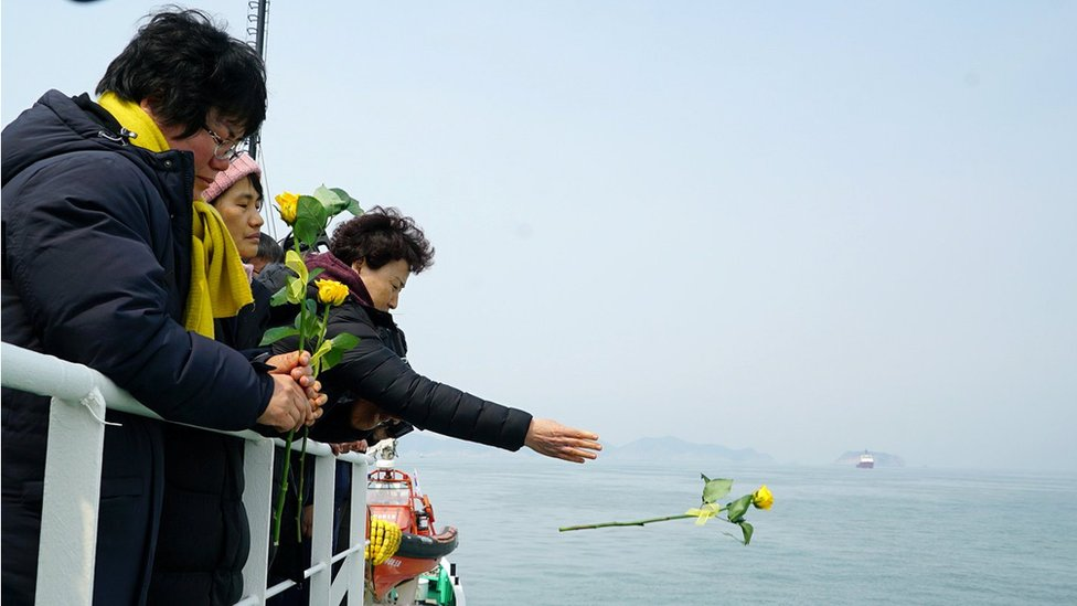 A family member of victims drops a yellow flower into the sea during a memorial ceremony at sea off Jindo, South Korea, in this handout picture provided by the Ministry of Oceans and Fisheries and released by Yonhap on March 28, 2017.