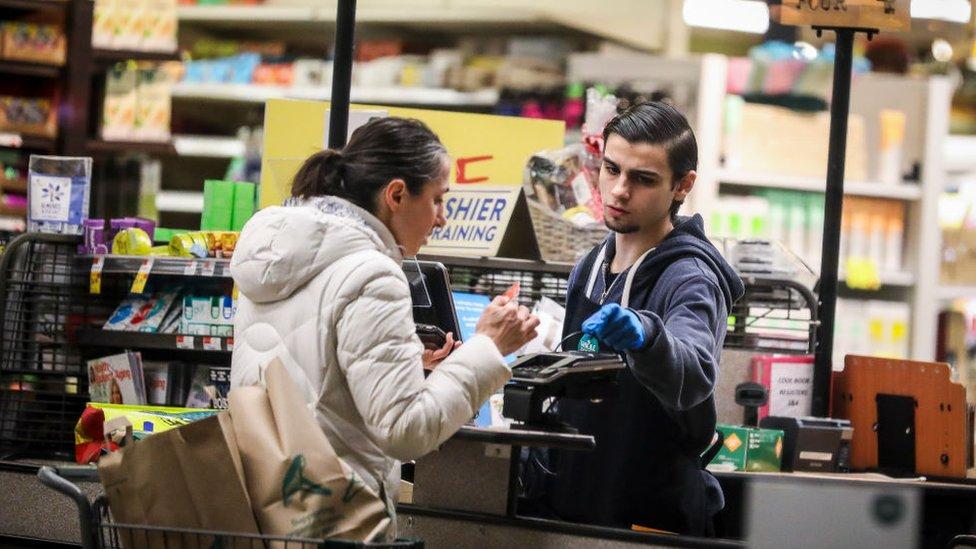 Un empleado de Whole Foods atiende a un cliente.
