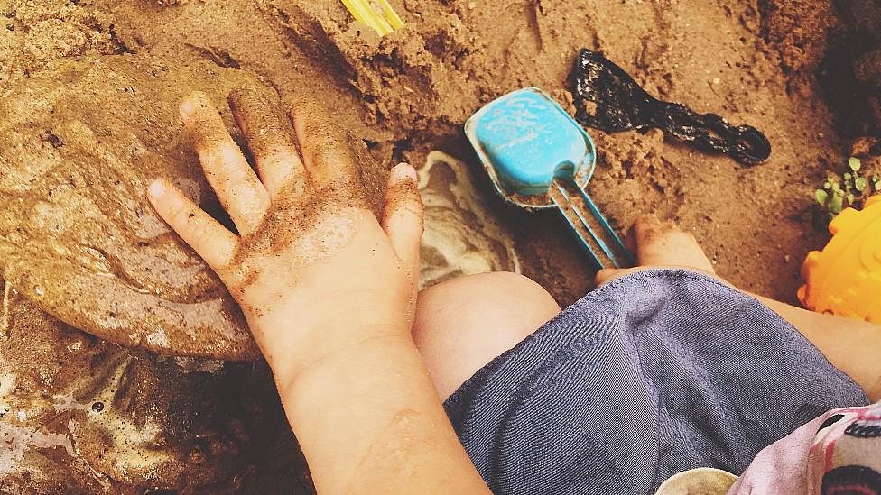 Mano de un niño jugando con tierra