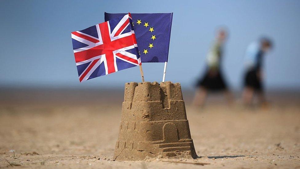 Sandcastle with Union flag and EU flag