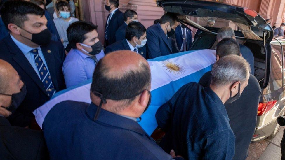 Pallbearers carry the casket of soccer legend Diego Maradona