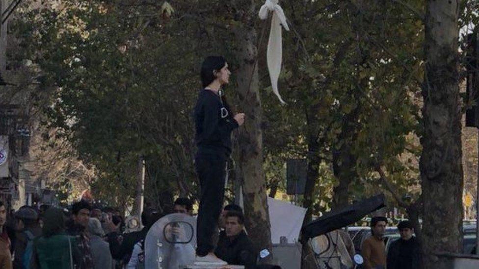 woman waving white headscarf