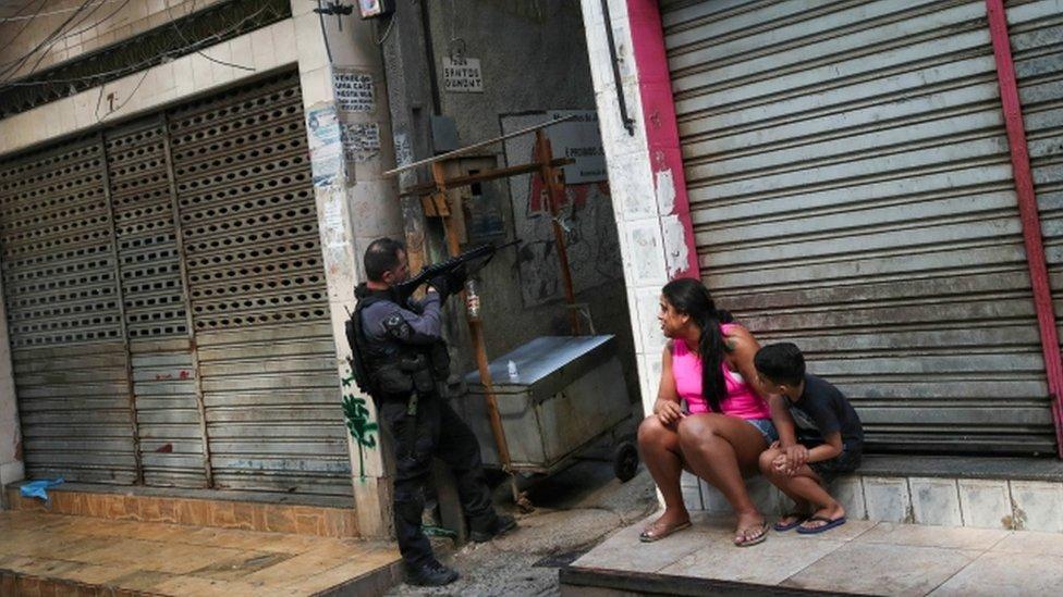Sentados em frente a loja fechada, mãe e filho observam policial ao lado apontando arma grande