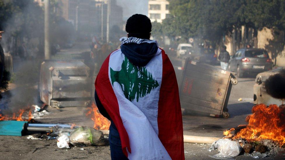 Un manifestante antigubernamental portando la bandera del país-