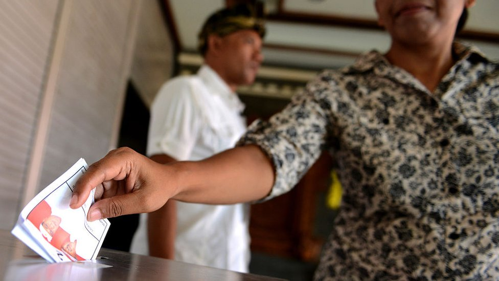 A Balinese woman casts her ballots at a polling station in Kuta on Indonesia's resort island of Bali on December 9, 2015