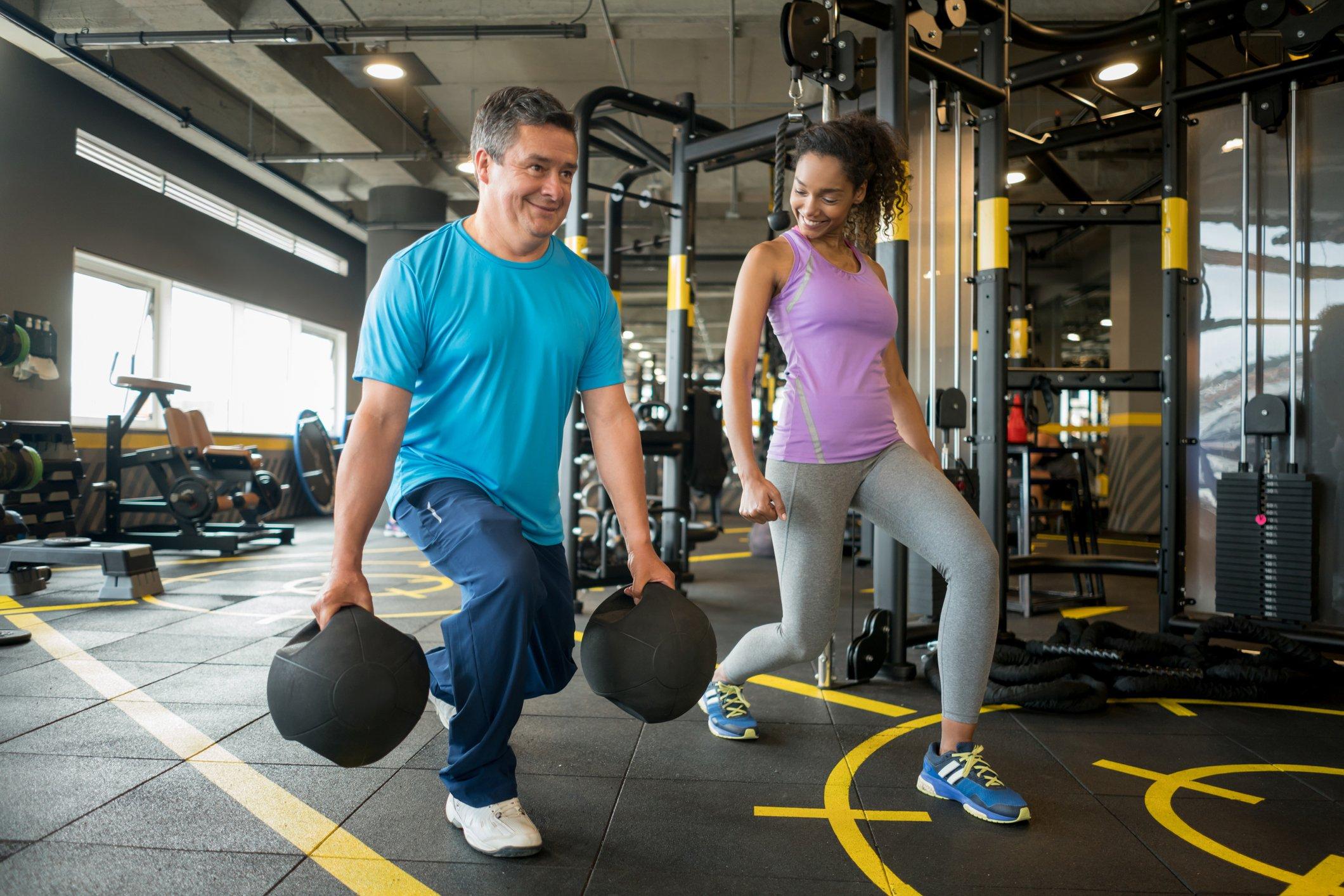 Hombre y mujer haciendo ejercicios para piernas en un gimnasio