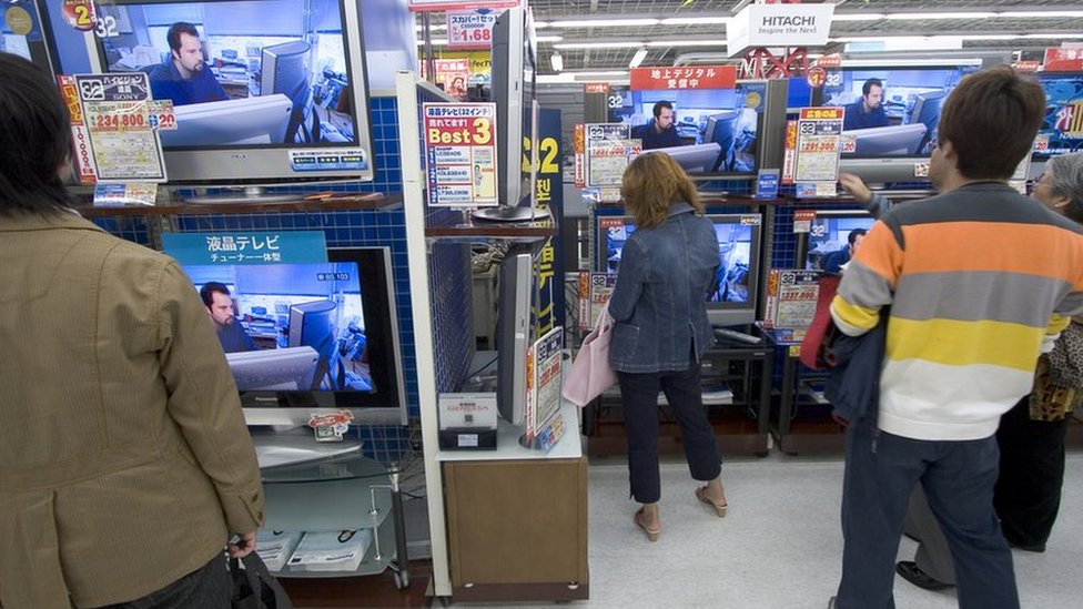 Shoppers look at televisions in Tokyo