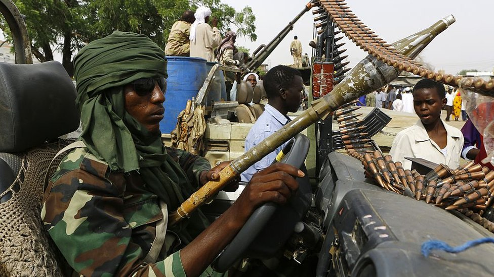 A fighter from the Sudanese Rapid Support Forces sits in an armed vehicle in the city of Nyala, in south Darfur, on May 3, 2015, as they display weapons and vehicles they say they captured from Dafuri rebels and fighters from The Justice and Equality Movement (JEM), lead by opposition leader Jibril Ibrahim, the previous week