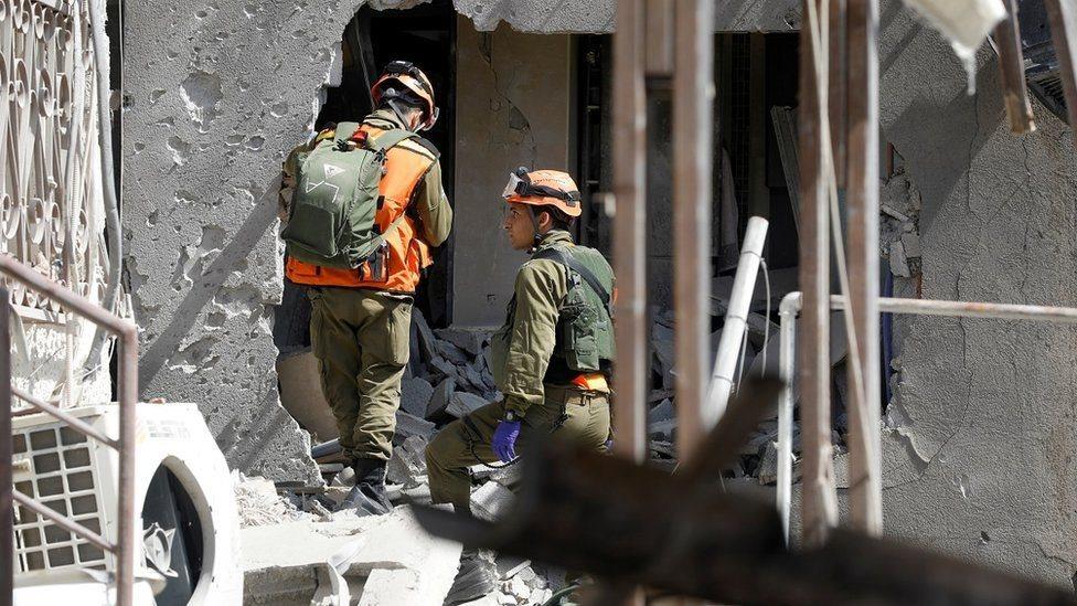 Tentara Israel memeriksa gedung yang rusak di kota Ashkelon akibat roket Hamas.
