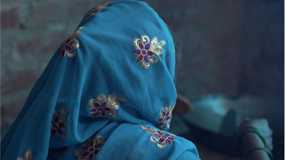An image of the mother from the back of her head where she's wearing a blue headscarf