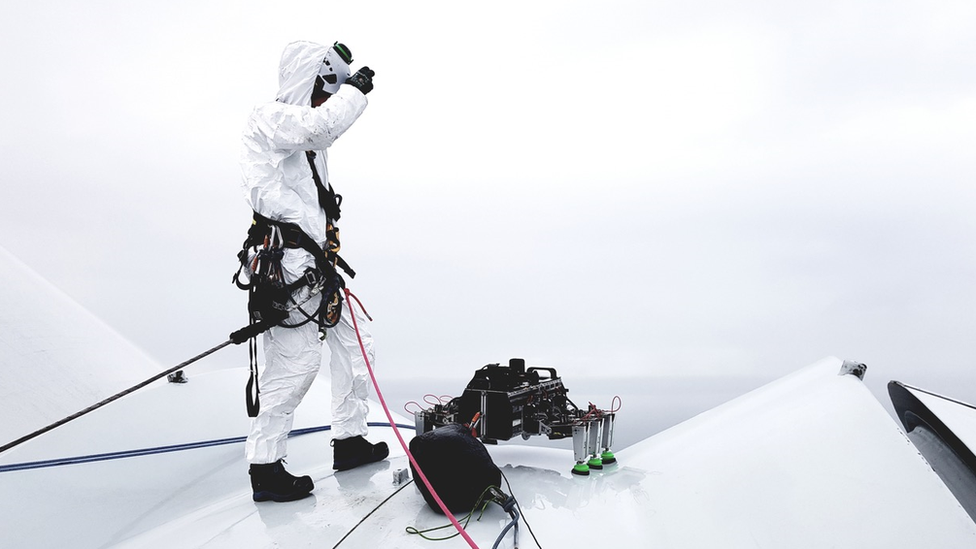 BladeBUG robot on a wind turbine with a man operating the device