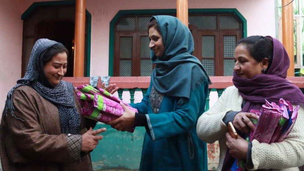 Irfana giving pads to a Kashmiri woman