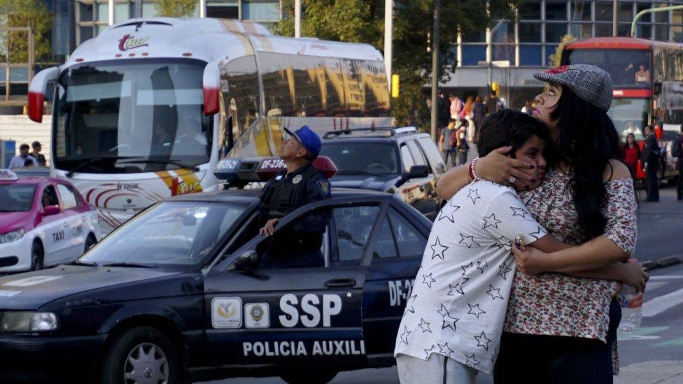 Una mujer abraza a un niño durante un sismo en México