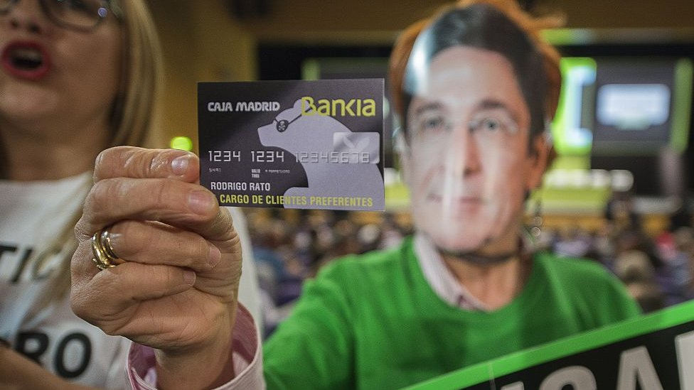 A woman displays a fake Bankia credit card of Rodrigo Rato as she protests against fraud during the Bankia Shareholders Extraordinary General meeting in Valencia on 22 April 2015