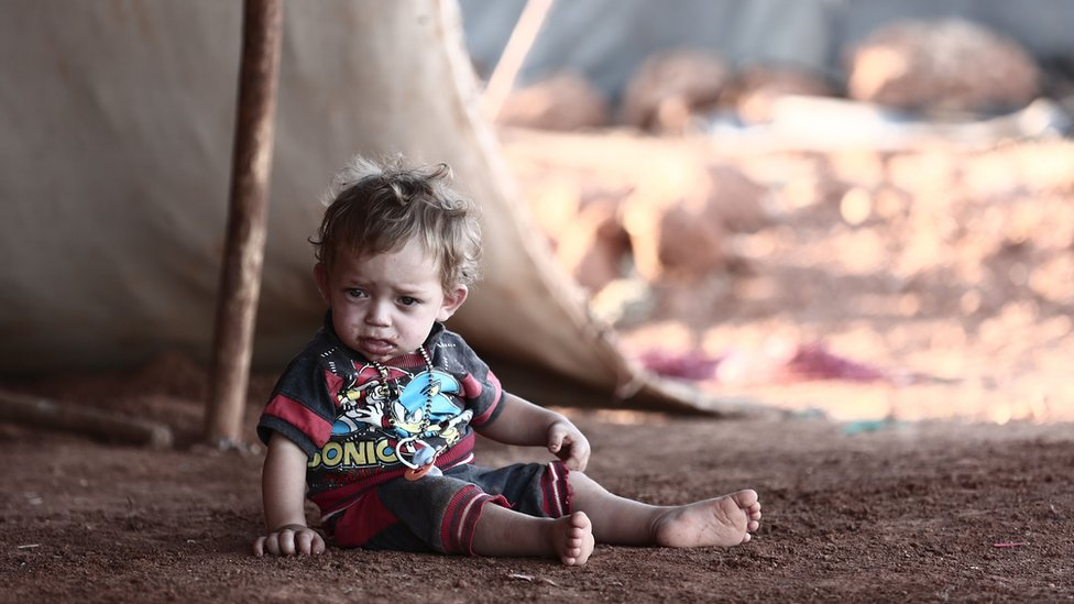 A child sits in front of a tent at a camp for the displaced in the province of Idlib
