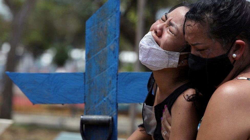 Kelvia Andrea Goncalves, 16, uma jovem de cabelos lisos e pretos, de máscara, chora de olhos fechados e com expressão de grande dor, e é abraçada pela tia, uma mulher de meia idade e cabelos pretos, em frente a uma cruz de madeira azul que marca o túmulo da mãe, no cemitério Parque Taruma, em Manaus