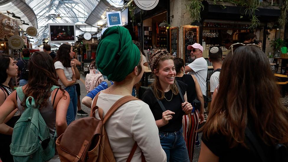 Meninas sem máscaras em um mercado em Jerusalém em abril