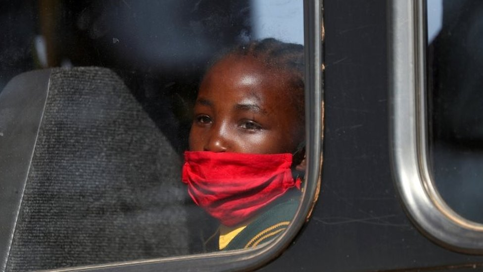 A girl wearing a mask looks through a bus window at Eikenhof in southern Johannesburg, South Africa.  Photo: August 2020