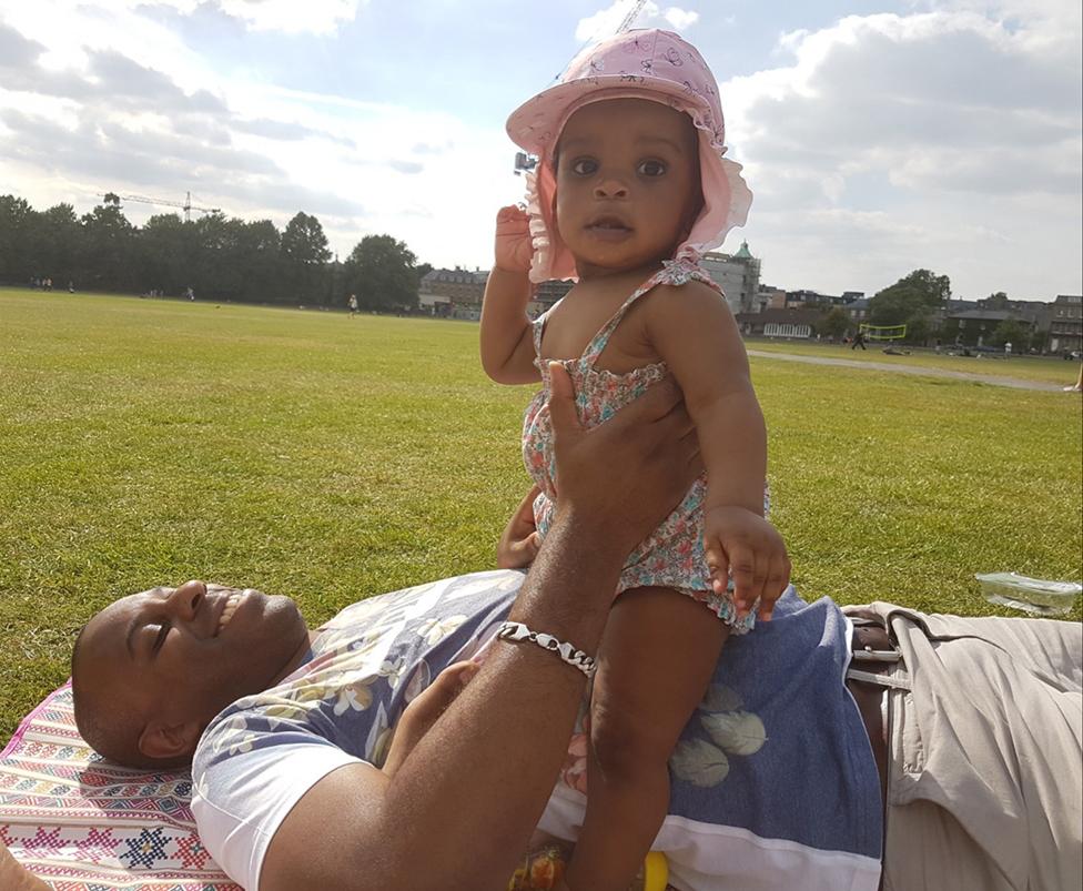 Elliott tumbado en el césped con su hija sentada sobre su vientre