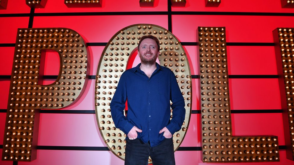 Chris McCausland standing in front of the Live at the Apollo sign.