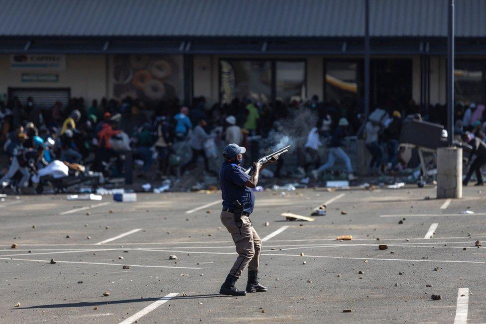 Un miembro de la policía de Sudáfrica dispara balas de goma contra un grupo que saqueó el centro comercial Jabulani en Soweto, al suroeste de Johannesburgo, el 12 de julio de 2021.
