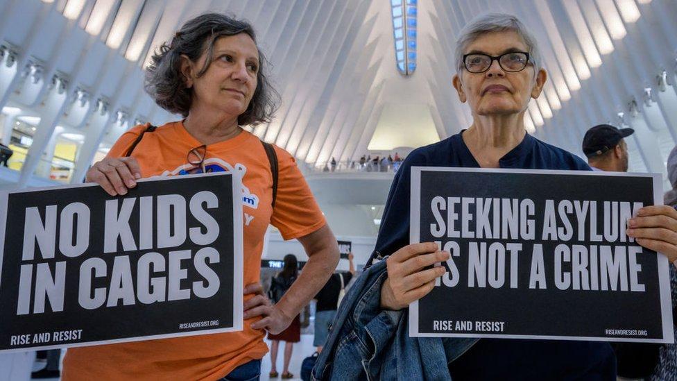 Dos mujeres participan en una protesta contra la política de detención de menores de Trump.