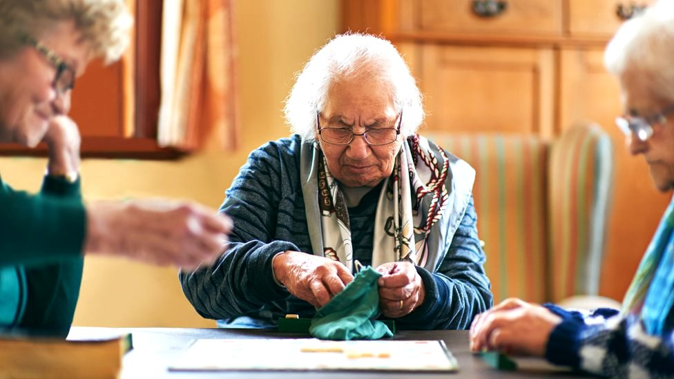 Elderly people, in a care home, play a board game