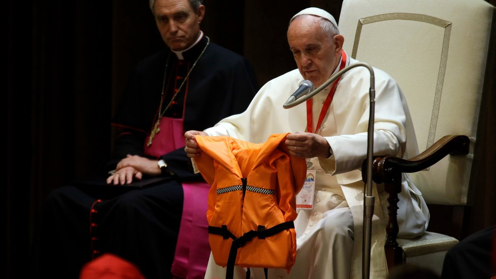 """Pope Francis holds a life jacket which was donated to him by a migrants"""" rescuer during a meeting with some 400 children coming by train from the region of Calabria, at the Vatican"""