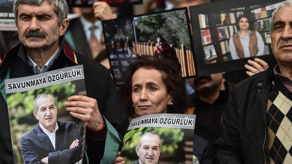 """Protesters hold poster portraits of Cumhuriyet""""s chairman Akin Atalayas they attend a demonstration at the courthouse in Istanbul on March 15, 2018."""