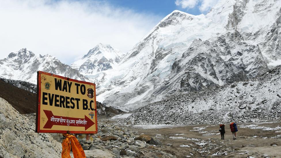 """Dos montañistas en una ruta hacia la cumbre del Everest y un cartel que señala """"Camino hacia el Everest"""""""