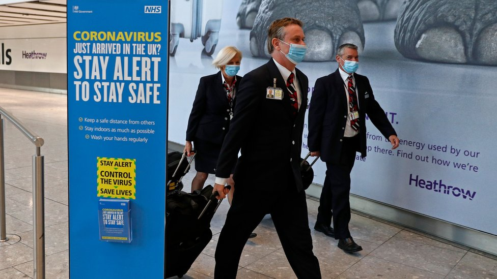 British Airways flight crew wear protective facemasks as they arrive at Terminal 5 at Heathrow airport