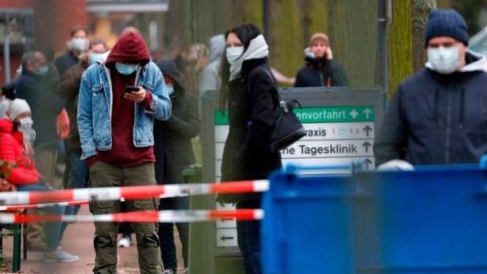 Almanya'da maskeleriyle yürüyen insanlar