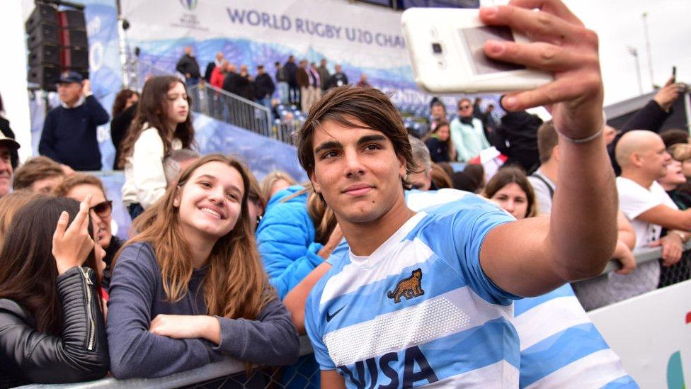 Jugador de rugby argentino haciéndose una selfie con fans