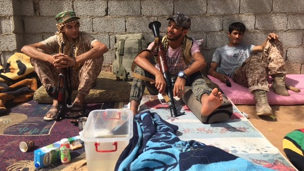 three men with weapons lounging in the sunlight, June 2016