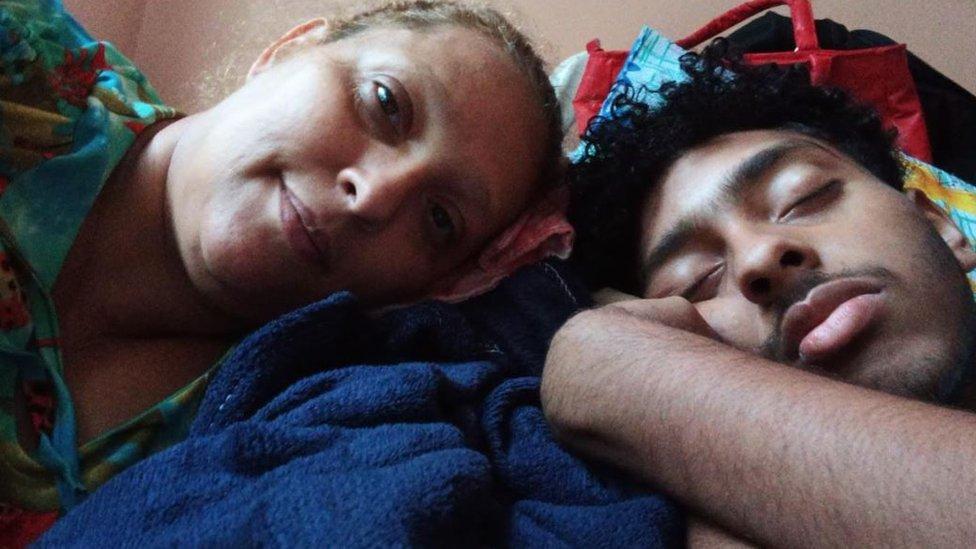 Elisangela está deitada com os olhos abertos e a cabeça encostada na de seu filho, Mateus, que está dormindo