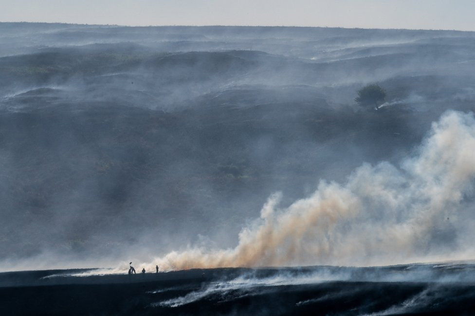 A distant view of Winter Hill near Bolton, shows the massive task firefighters are facing to control hundreds of smouldering embers on 2 July 2018.