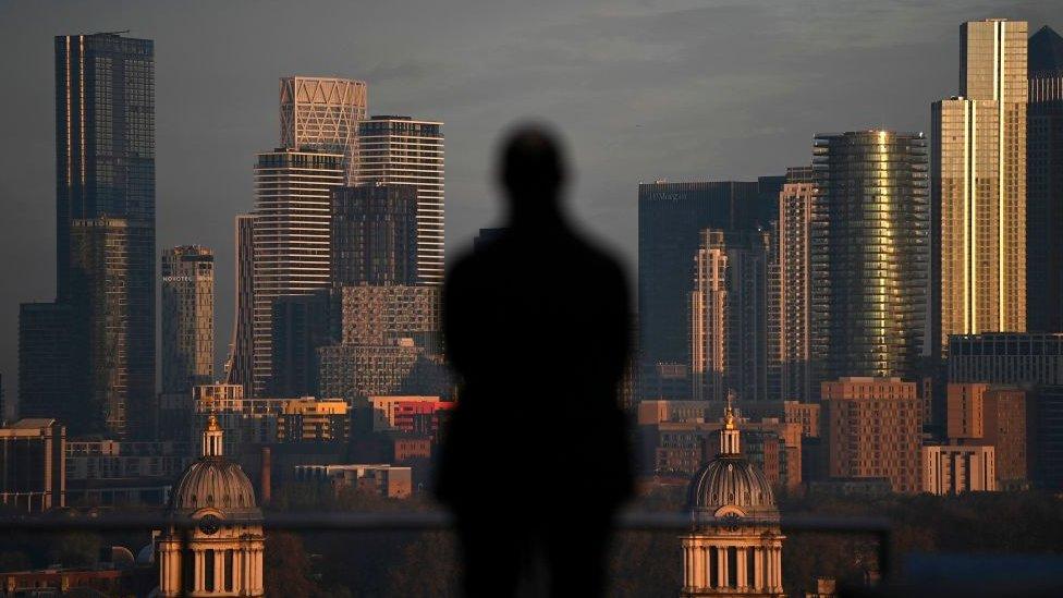 Hombre mirando hacia Canary Wharf, una de las zonas financieras de Londres.