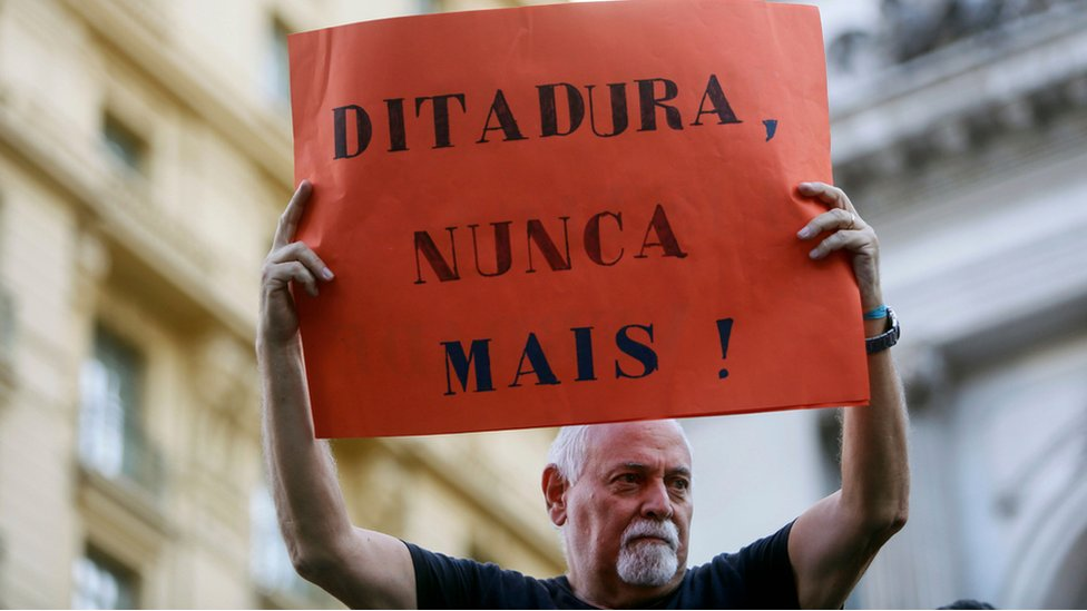 """Hombre con cartel de """"Dictadura, nunca más"""""""