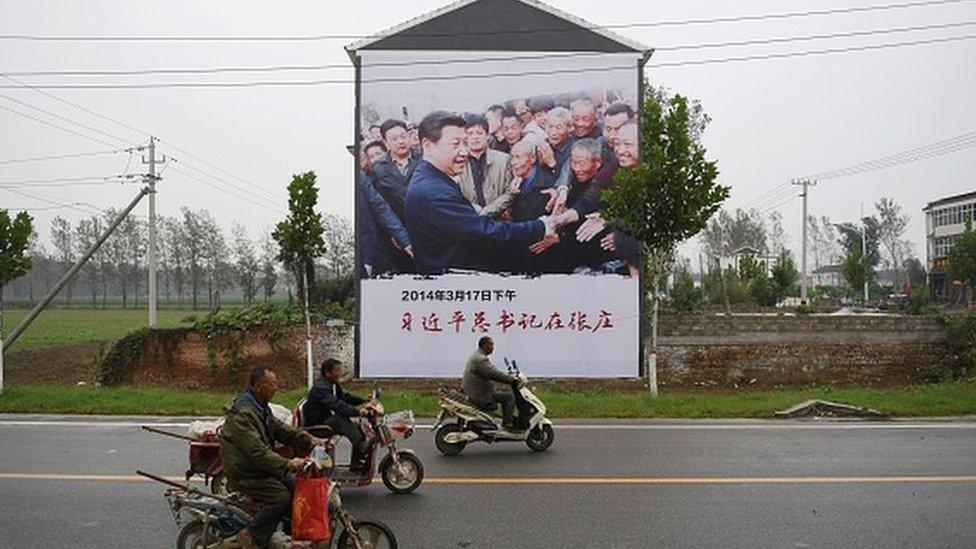 Una pancarta del presidente Xi Jinping visitando gente que vive en pobreza
