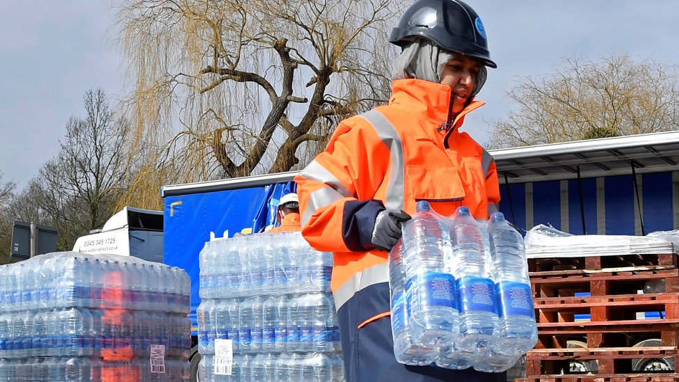 A Thames Water operative collects bottled water for distribution in Hampstead in London, Britain